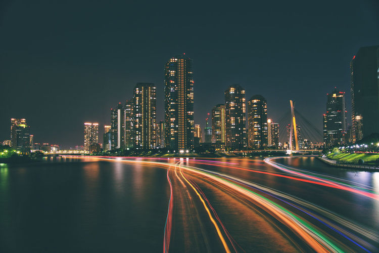 Illuminated light trails on city buildings at night