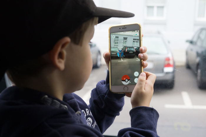 Five year old boy playing Pokemon Go on a public bus in Berlin, Germany as the augmented reality app was released by Nintendo for the German market. App Augmented Reality Boy Child Game IPhone Kid Leisure Activity Mobile Phone Nintendo Playing Pokemon Go Pokémon Screen Smart Phone Technology Using Phone Wireless Technology