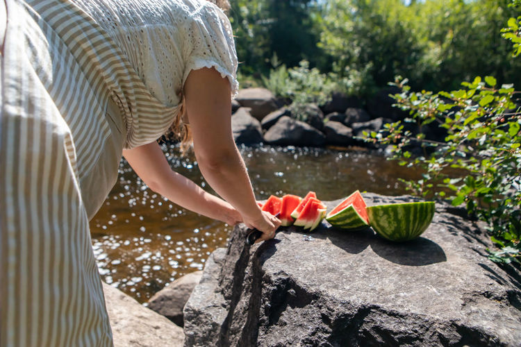 Midsection of woman cutting watermelon by river