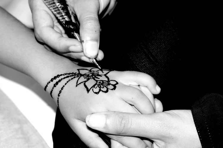 Midsection of person applying henna tattoo on child hand
