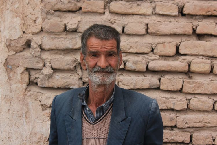 Portrait of senior man standing against brick wall