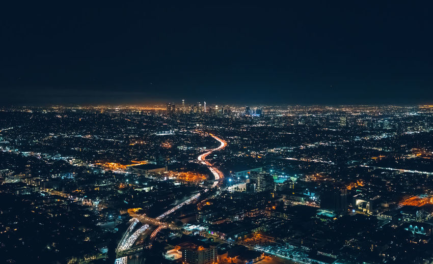 Aerial view of illuminated highway amidst buildings in city at night