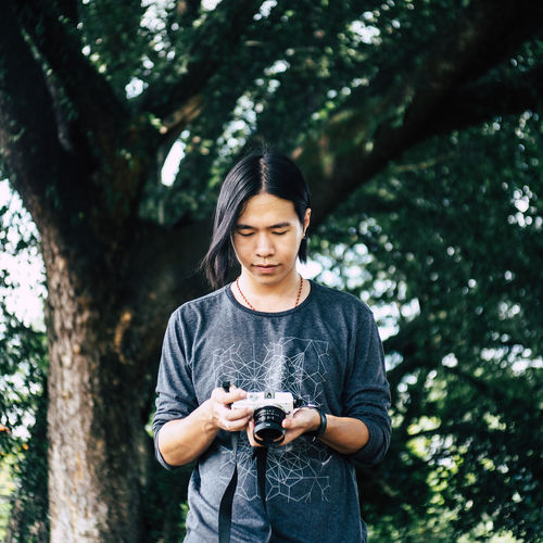 Camera - Photographic Equipment Casual Clothing Day Digital Camera Focus On Foreground Front View Holding Leisure Activity Lifestyles Modern Nature One Person Outdoors Photographer Photographing Photography Themes Portrait Real People Standing Technology Tree Young Adult