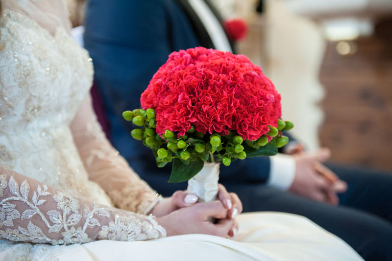 Midsection Of Bride And Groom With Carnation Flower Bouquet During Wedding Ceremony