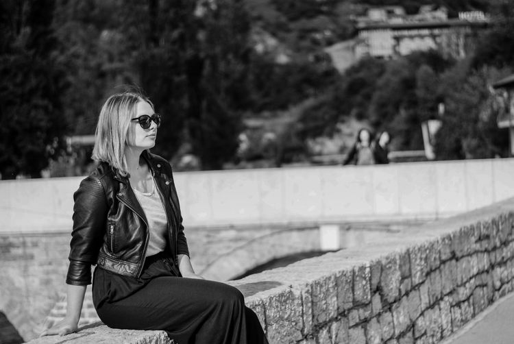 Side view of woman wearing sunglasses while sitting on stone wall