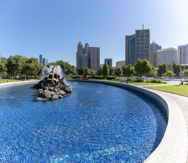 View of swimming pool in city against clear sky