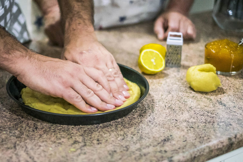 Cropped hands of man kneading dough in plate
