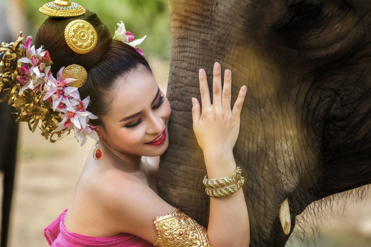 Smiling young woman in traditional clothes holding elephant trunk
