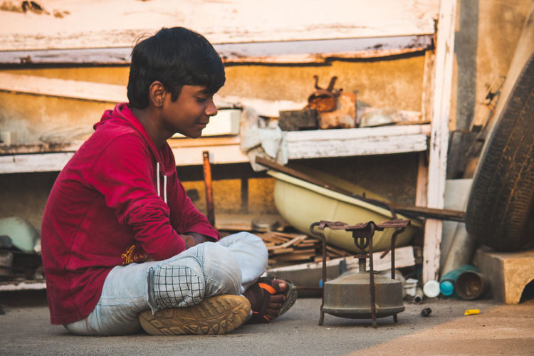Side view of boy sitting with old stove