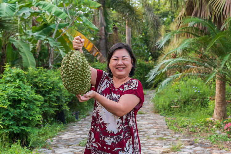 Portrait of happy mature woman holding durian while standing on footpath amidst plants