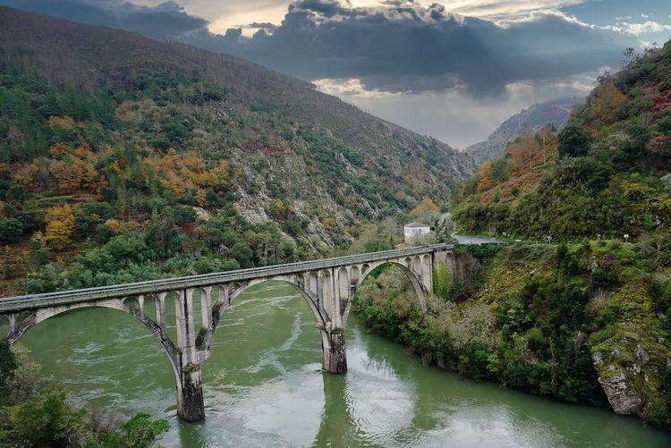 Bridge over river amidst mountains