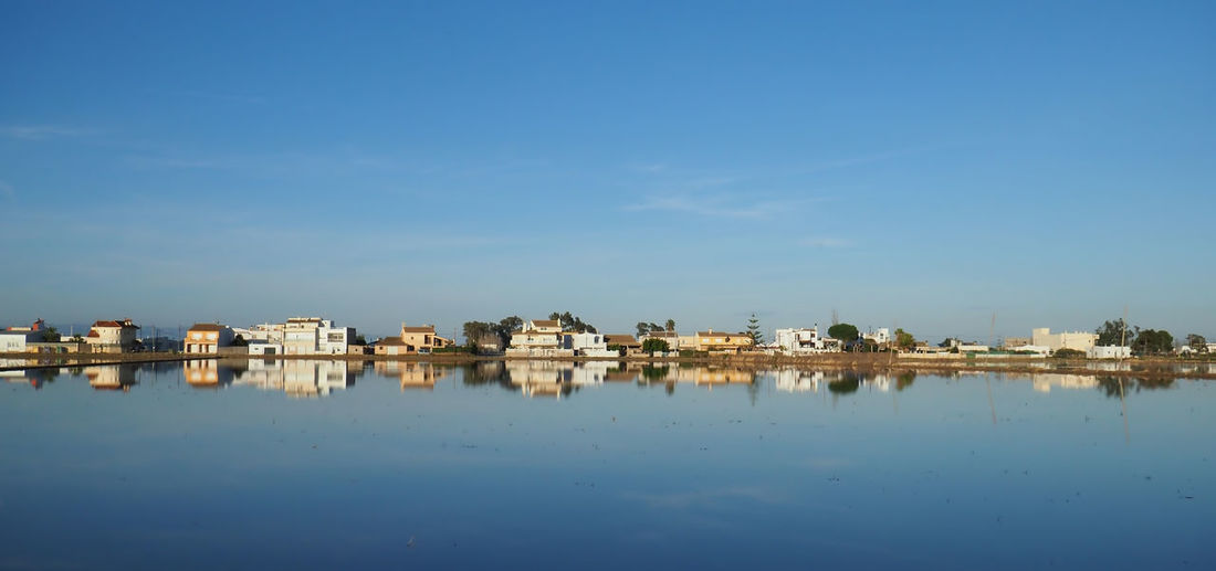 Reflection of buildings in sea against blue sky