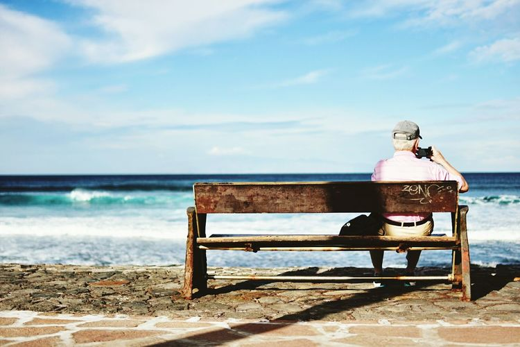 Man sitting on bench at the seaside