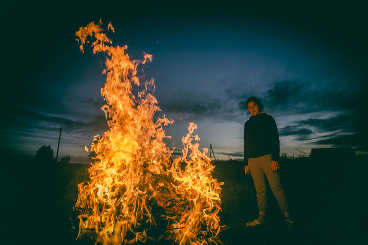 Woman standing by bonfire against sky at night