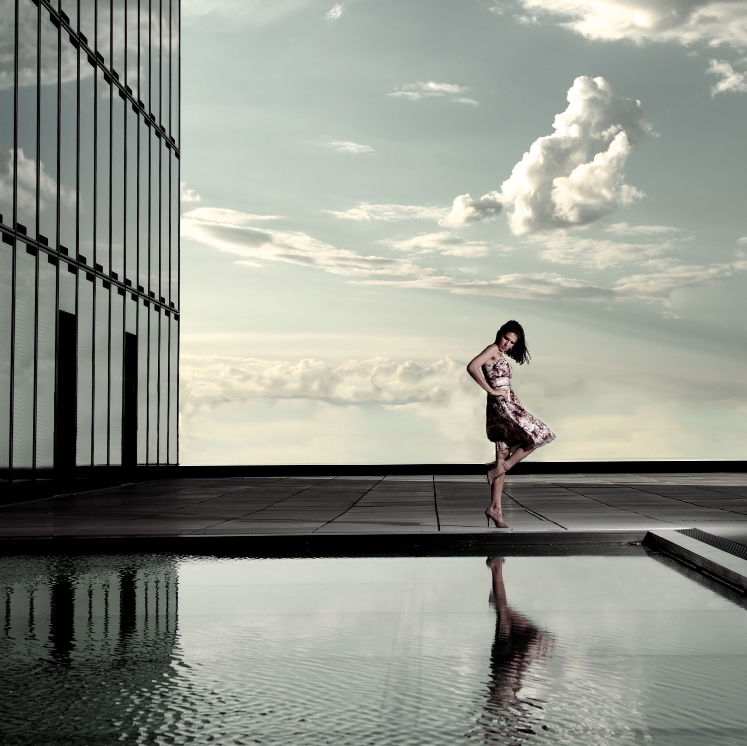 full length, lifestyles, leisure activity, young adult, sky, water, built structure, jumping, casual clothing, architecture, building exterior, standing, person, side view, cloud - sky, waterfront, young women, day