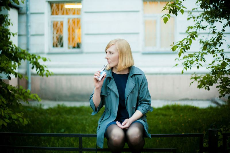 Architecture Bad Habit Beautiful Woman Blond Hair Building Exterior Built Structure Casual Clothing Day Focus On Foreground Holding Lifestyles One Person Outdoors People Real People Sitting Technology Three Quarter Length Tree Wireless Technology Women Young Adult Young Women