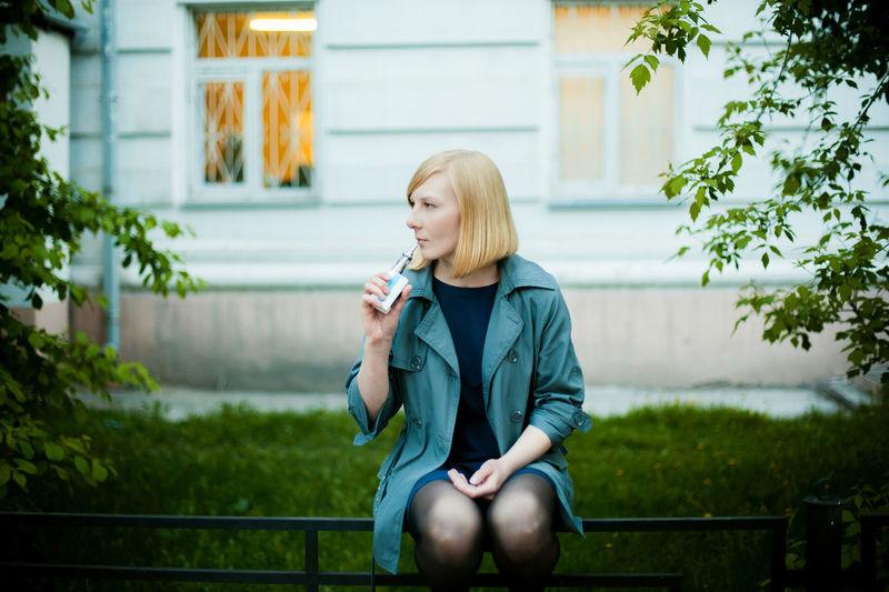 Beautiful young woman smoking electronic cigarette