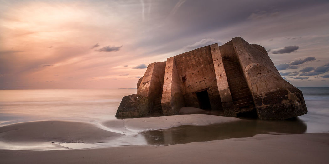 Bunker Beauty In Nature Cloud Cloud - Sky Coastline Horizon Over Water Nature No People Outdoors Rock - Object Rock Formation Sea Shore Sky Sunset The KIOMI Collection Tranquility Water