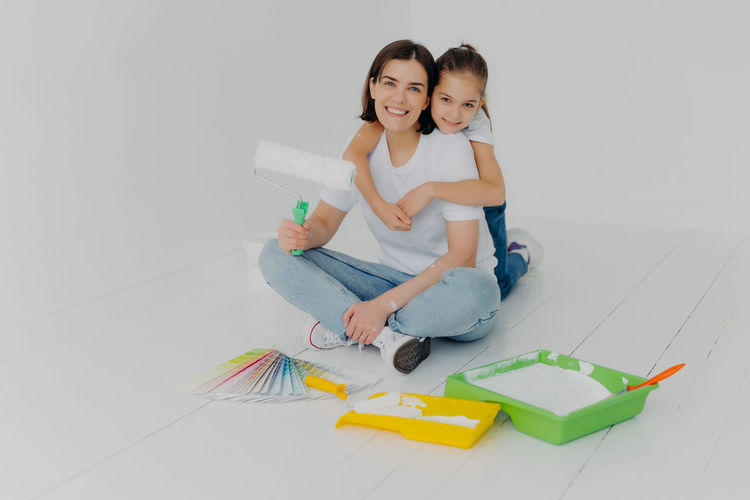 Portrait of mother and daughter with paint rollers