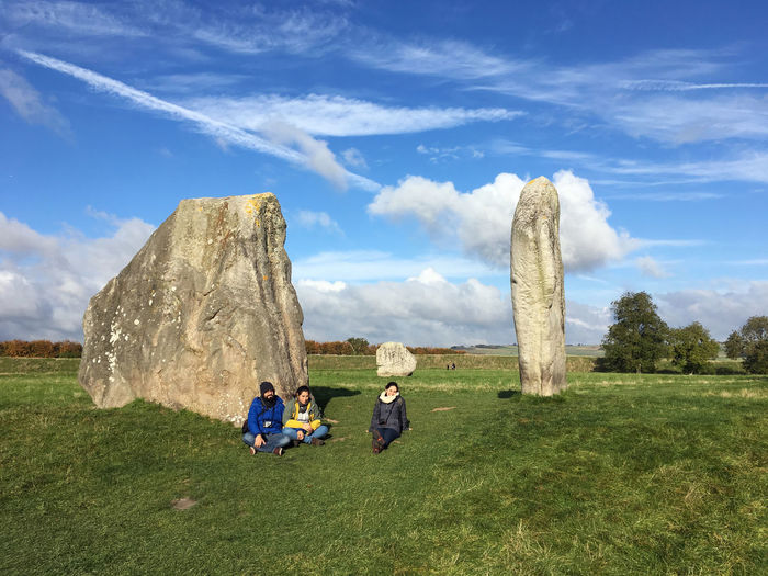 Friends sitting on grassy field against sky at avebury stone circle