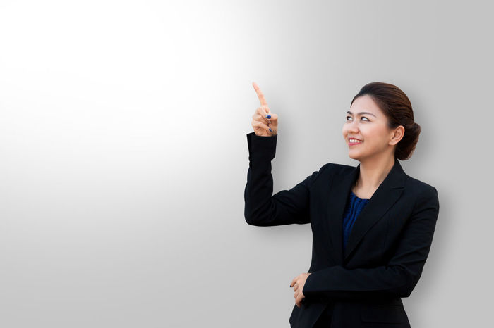 Business woman is wag and looking in suit Asian  Copy Space Crossed Isolated Smart Suit Thai Advertisement Arms Raised Business Businesswoman Closeup Color Concept Fingers Looking Up Manager Pointing Portrait Secretary Smiling Studio Shot Suit Waist Up Women