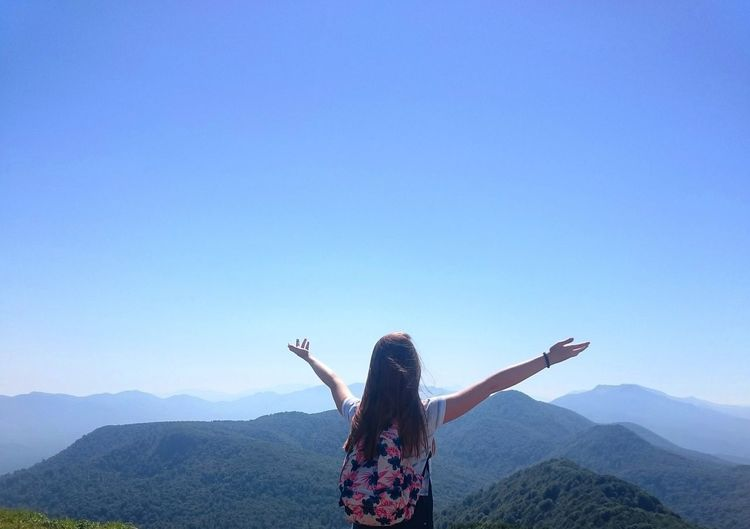 Rear View Of A Woman Raising Hands Against Blue Sky
