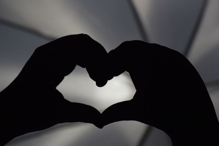 Close-up of silhouette hand holding heart shape against black background