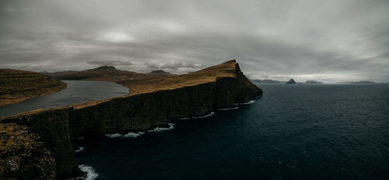 When I came to the Faroe Islands, I remembered some spots that I had to visit. Places that I've seen in the time line of my photographer friends or while browsing through endless inspirational tumblr feeds. One of them was the lake of Sørvágsvatn. I reached the high point within an hours walk and the nearer I got to the coastline, the more excited I became. The sky was all grey, releasing rain drops from time to time. And the wind became stronger and stronger. I turned to the left and went to the edge. Down in the deep hit the Atlantic ocean against the cliffs. In front of me: Sørvágsvatn floating above sea level. Shaking legs & perspective happiness. Welcome to the Faroe Islands. Now on my blog. Atlantic Ocean Beauty In Nature Coastline Day Faroe Islands Mountain Nature No People Outdoors Panorama Scenics Sea Sky The Great Outdoors - 2017 EyeEm Awards Tranquil Scene Tranquility Water Waterfront