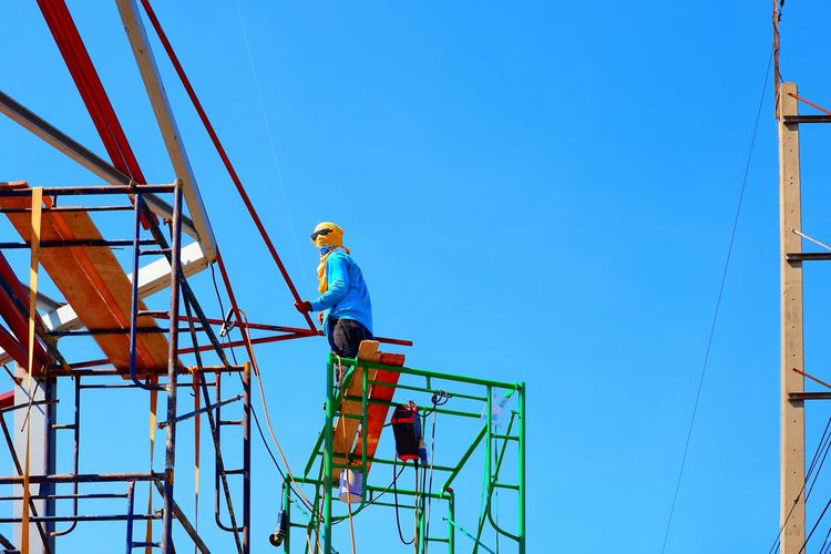 Low angle view of construction worker with sunglasses and yellow veil on high scaffold is working to build roof building structure against blue sky background, danger and risky work concept Occupation Roof Structure Building Metal Holding Electric Pole Blue Sky Sunny Day Lifestyle Sunglasses Veiled High Scaffolding Low Angle View Danger Risky Work Concept EyeEm Selects Manual Worker Working Clear Sky Full Length Scaffolding Construction Incomplete Construction Site Construction Equipment Construction Frame Worker