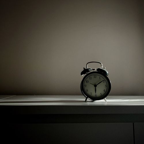 Close-up of alarm clock on table at home