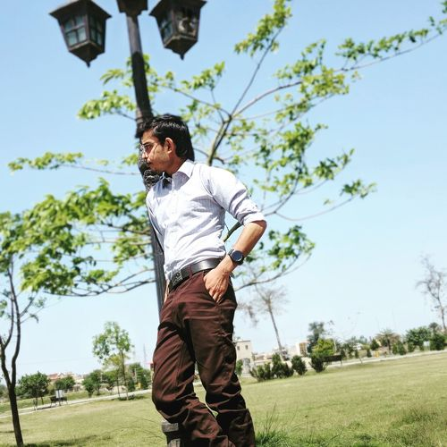 Low angle view of young man standing by street lamp on field against sky