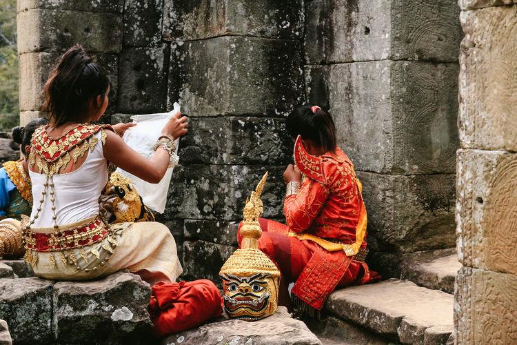 Rear view of women sitting outside temple
