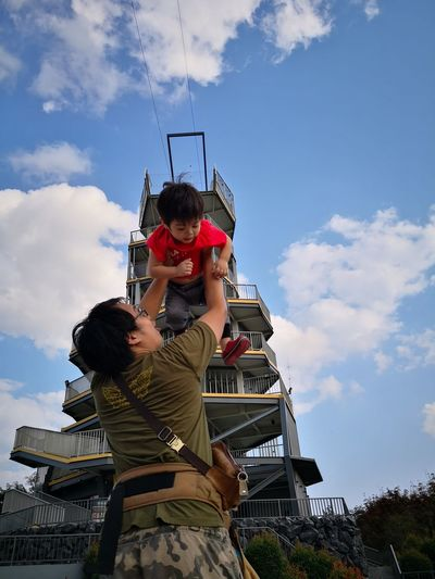 People on traditional windmill against sky