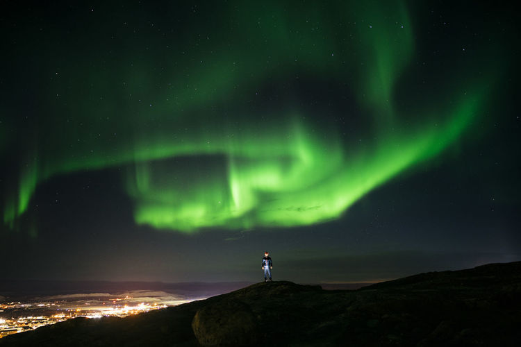 Man standing on mountain against aurora borealis