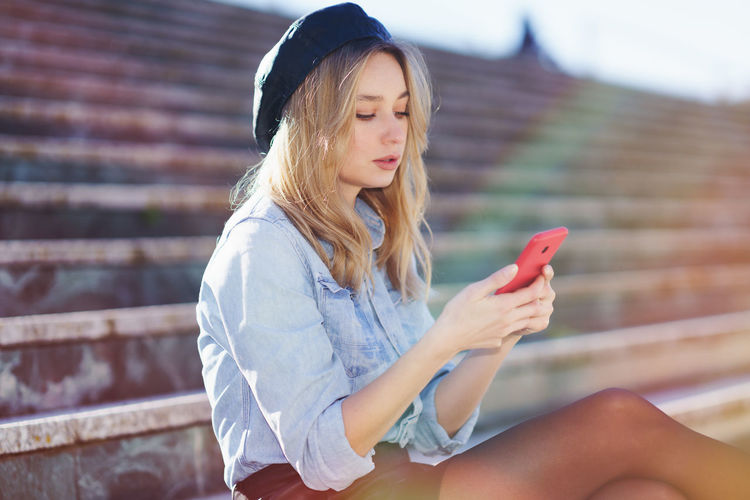 Beautiful young woman using mobile phone while siting outdoors