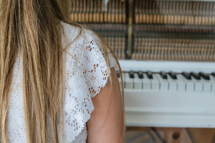 Cropped Image Of Woman Sitting By Grand Piano At Home