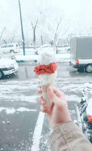 Close-up of hand holding ice cream cone at street