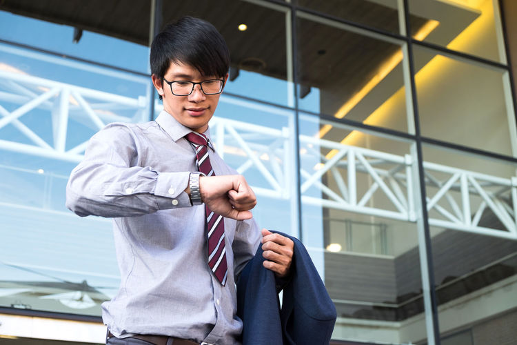 Businessman Checking Time Outside Office Building