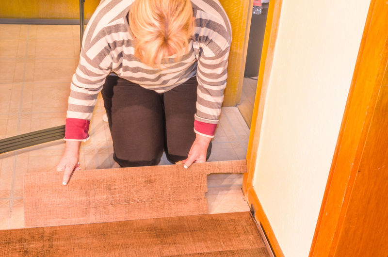 High angle view of woman kneeling while positioning plank on floor at home