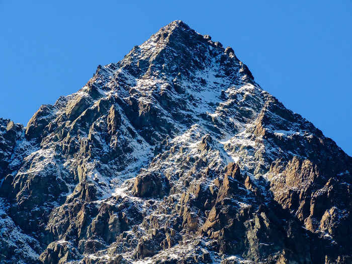 Low angle view of snowcapped mountain against clear blue sky, monviso, italy
