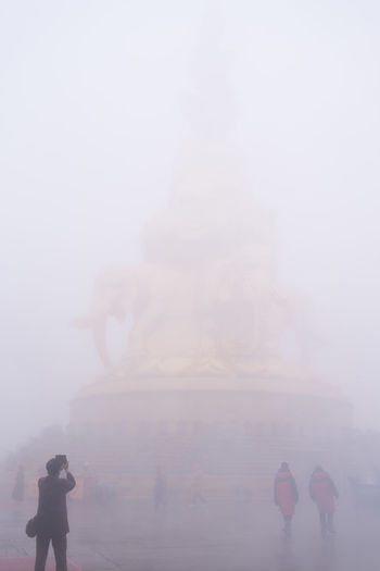 Tourist taking photo of golden budda statue in heavy fog in China. Golden Heavy Fog Statue Worship Budda Buddist Elephant Fog Lifestyles Photographing Real People Rear View Religion Tourism Travel Unclear
