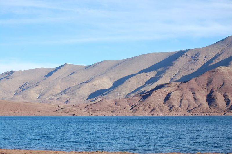 Scenic view of lake and arid mountains against blue sky