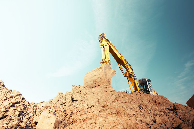 Construction site Construction Site Excavator Working Hard Workplace Blue Brown Color Construction Industry Construction Vehicle Copy Space Day Deserted Dirt Earth Mover Excavator Shovel Grabber Hydraulics  Industry Low Angle View No People Outdoors Rock Sky Soil Solid Sunlight