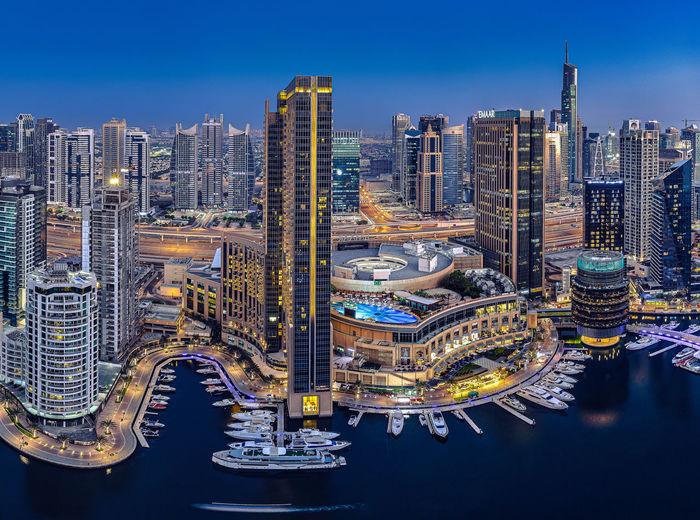 Illuminated city buildings against blue sky