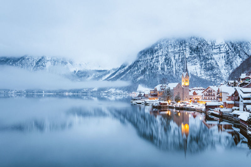 Scenic view of lake by buildings against sky during winter