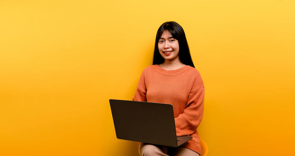 Smiling young woman using mobile phone against yellow background