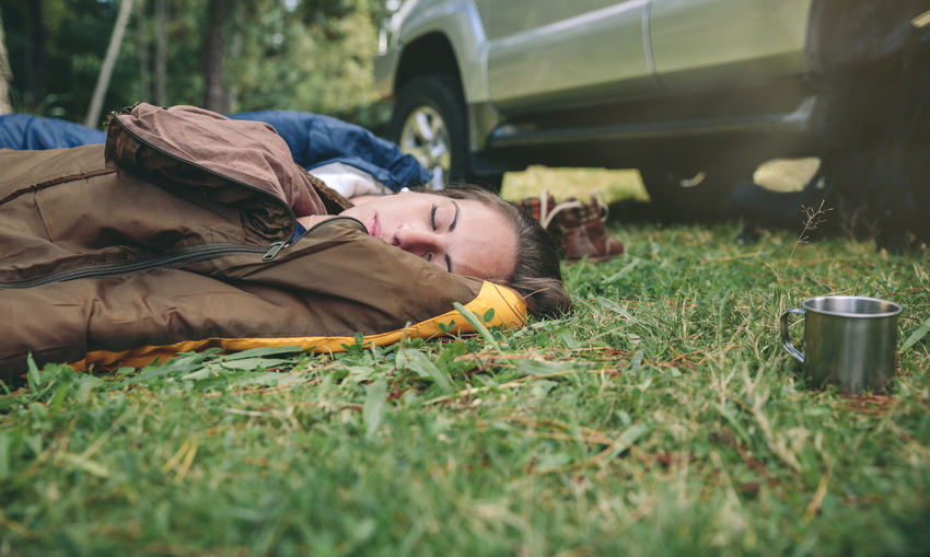 Closeup of young beautiful woman sleeping in the nature inside of sleeping bag over the grass Camping Campsite Grass Hiking Horizontal Nature Travel Trip Woman Adventure Backpack Bag Camp Car Caucasian Equipment Female Forest Mountain Off Road One People Sleeping Tent Vehicle Young Adult