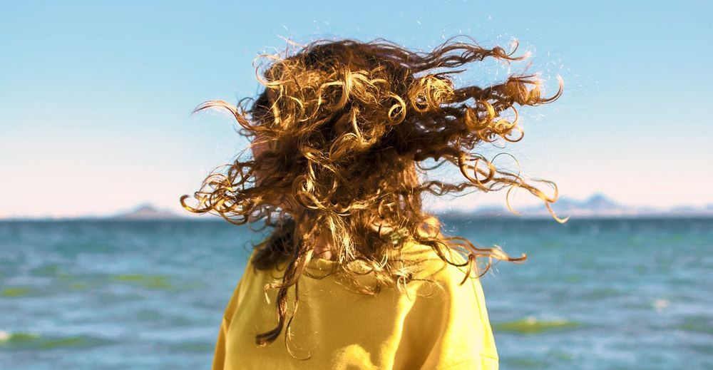 Woman shaking head while standing against sea