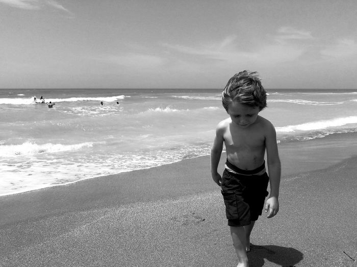Full Length Of Shirtless Boy Playing On Beach Against Sky
