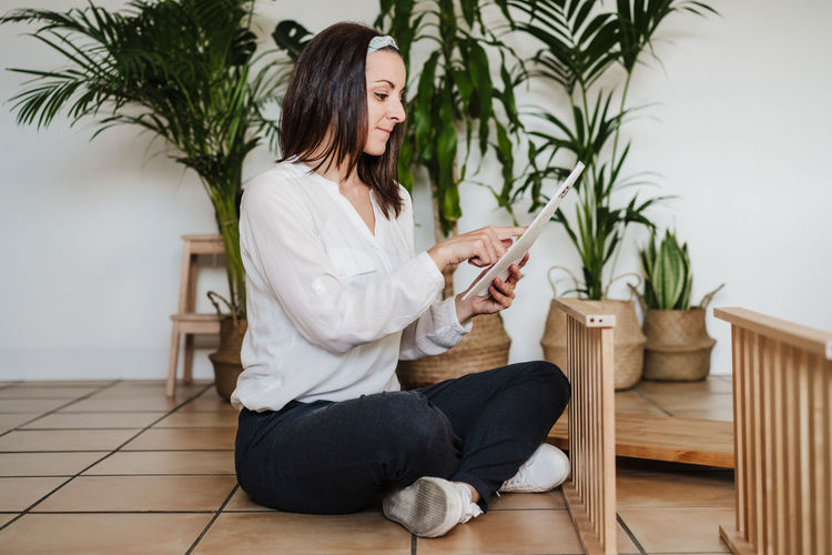 Woman using phone while sitting on wooden floor at home